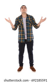 Full length shot of a happy handsome young man looking up and rising his hands, guy wearing caro shirt and jeans with brown shoes, isolated on white background