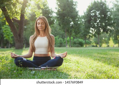 Full length shot of a happy healthy beautiful woman meditating in lotus position outdoors. Beautiful woman relaxing, meditating in the park, sitting on the grass