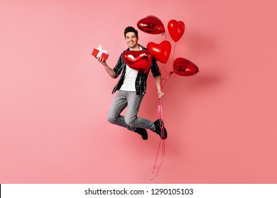 Full length shot of happy man celebrating valentine's day. Smiling guy jumping with red balloons.
