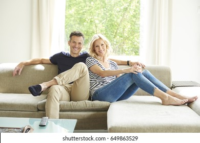 Full length shot a happy mature couple sitting on couch at home and relaxing togetherness.