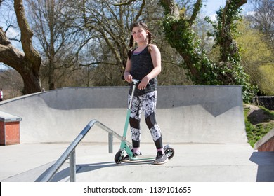 Full length shot of a happy sporty young girl with plaits at a skate park with her scooter in Winchester in the UK