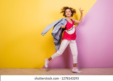 Full length shot  happy woman in  white jeans and pink shirt.  Ecstatic girl with short curly hairstyle fooling around on  yellow and pink  background.