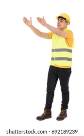 Full length shot of a happy young engineer smiling and holding and rising his hands, guy wearing yellow t-shirt and jeans with yellow vest and helmet, isolated on white background