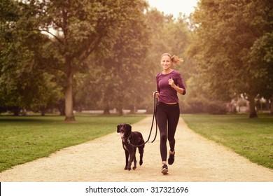 Vollständiger Schuss einer gesunden jungen Frau, die mit ihrem schwarzen Haustier-Hund im Park joggt