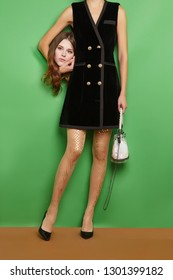 Full length shot of a lady holding her head with light brown hair. The woman is wearing a black blazer dress and tights with shiny print. The woman is posing on green background, standing on brown flo