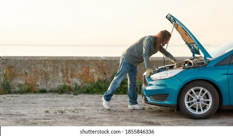Full length shot of man looking under the hood of his broken car, trying to repair it on his own while standing alone after car breakdown on the road side, Selective focus, Side view, Horizontal shot