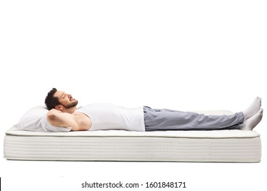 Full length shot of a man in nightwear sleeping on a mattress isolated on white background