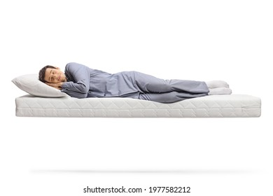 Full length shot of a man in pajamas sleeping peacefully on a floating mattress isolated on white background