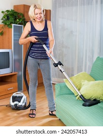 full length shot of   mature woman cleaning with vacuum cleaner at home