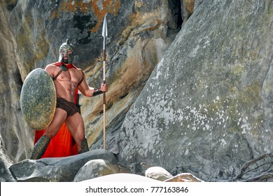 Full length shot of a medieval warrior in battledress holding a shield and a spear standing on top of the rock looking away copyspace safety guard protection bravery muscles athletic body.