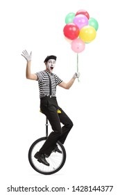 Full length shot of a mime on a unicycle holding a bunch of colorful balloons and waving at the camera isolated on white background