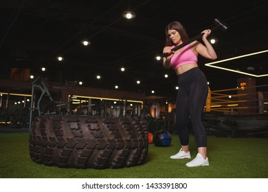 Full length shot of a plus size young sportswoman hitting huge wheel tire with a sledgehammer, copy space. Attractive curvy woman doing crossfit workout with a sledgehammer