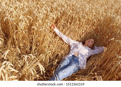 Full length shot of a pretty teenage girl enjoying the outdoors. Caucasian girl wearing a blue jeans and white shirt lying in wheat field. People, travel, freedom concept.