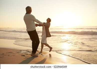 Full length shot of romantic senior couple enjoying a day at the beach. Mature couple enjoying their vacation on the beach.