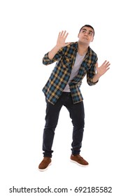 Full length shot of a scared handsome young man looking up and rising his hands, guy wearing caro shirt and jeans with brown shoes, isolated on white background