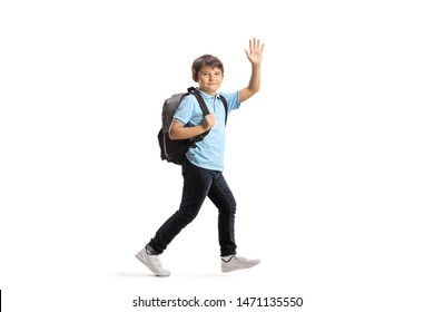 Full length shot of a schoolboy with a backpack running and waving at the camera isolated on white background
