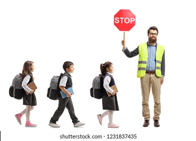 Full length shot of schoolchildren walking in a line and a teacher with safety vest and stop sign isolated on white background