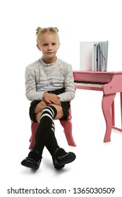 Full length shot of schoolgirl with ballet buns, wearing blouse with ruffles, black skirt and striped kneesocks. The girl is looking at camera, sitting near a piano on chair with her legs crossed.