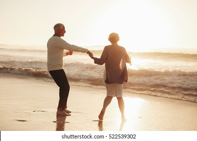 Full length shot of senior couple having fun at beach during sunset. Mature couple enjoying holidays together at sea shore.