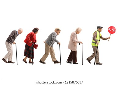 Full length shot of senior people walking in a line behind an elderly man with a safety vest and stop sign isolated on white background