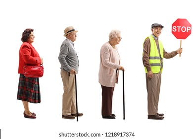 Full length shot of senior people waiting in line behind a man wearing safety vest and holding a stop sign isolated on white background