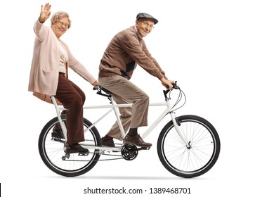 Full length shot of a senior woman and man riding a tandem bycicle and waving isolated on white background