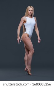 Full length shot of sexy shaped fitness bikini model in white gym leotard isolated on black background