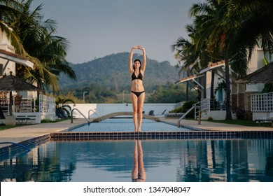 Full length shot of a slim young woman in swimwear at the poolside. Female athlete standing on the edge of the pool and looking away.