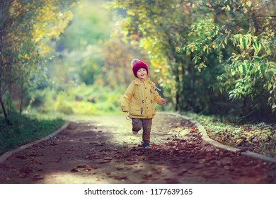 full length shot of small boy runnning on the path in the park