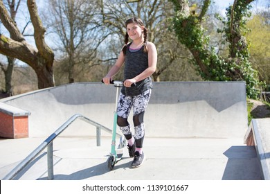 Full length shot of a smiling sporty young girl with plaits at a skate park with her scooter in Winchester in the UK
