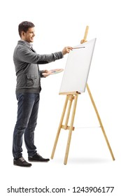 Full length shot of a smiling young man painting on a canvas isolated on white background