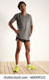 A full length shot of a tired muscular attractive black athlete in gray t-shirt, black shorts and neon green sneakers on white wall and light wooden floor background, hands on hips