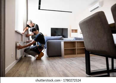 Full length shot of two professional plumbers, workers in uniform fixing or installing heating radiator. Construction, maintenance and repair concept. Selective focus. Horizontal shot