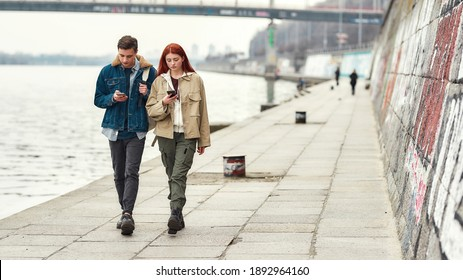 Full length shot of two teenagers totally absorbed in their smartphones, ignoring each other while walking along the riverside together. Technology, smartphone addiction. Selective focus. Web Banner