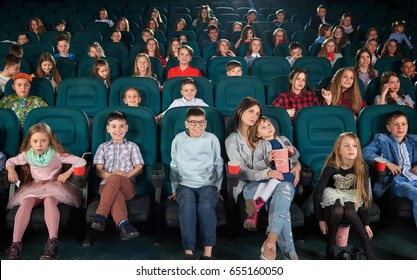 Full length shot of a woman enjoying watching a movie at the cinema with her little daughter in an auditorium full off children youth lifestyle leisure entertainment people activity concept.