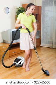 Full length shot of woman in skirt cleaning with vacuum cleaner at home