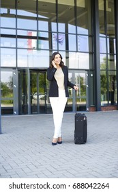 Full length shot of young businesswoman standing in front of business building and talking with somebody while waiting for the taxi.