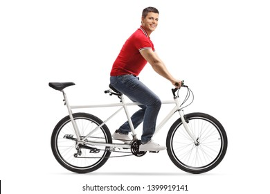 Full length shot of a young cheerful man riding a tandem bicycle alone and smiling at the camera isolated on white background