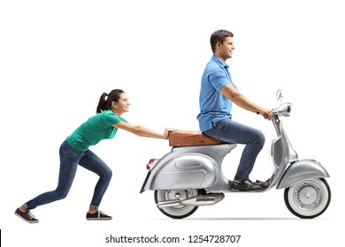 Full length shot of a young female pushing a guy on a vintage motorbike isolated on white background