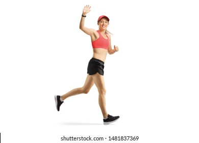 Full length shot of a young female in sportswear jogging and waving a the camera isolated on white background