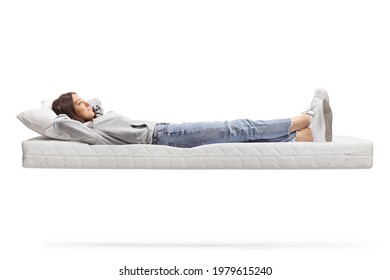 Full length shot of a young female in jeans resting on a floating mattress isolated on white background