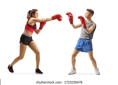Full length shot of a young girl and guy in sportswear fighting with boxing gloves isolated on white background