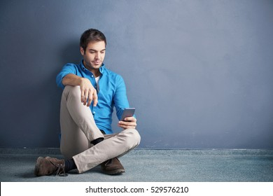 Full length shot of a young handsome man using his cellphone and texting message while sitting by the wall.