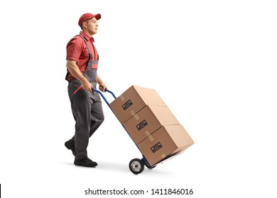 Full length shot of a young male worker in a uniform pushing boxes on a hand truck isolated on white background