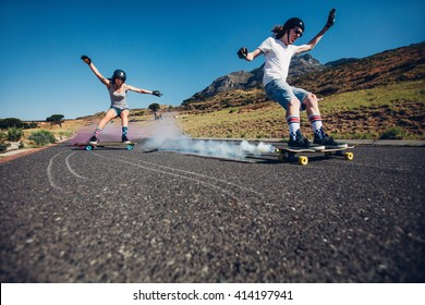 Full length shot of young man and woman outdoors longboarding down the road. Skate boards with smoke grenade. People practicing skating on rural road.