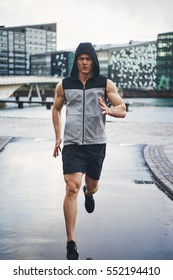 Full length shot of young man running down rainy street and looking at street.