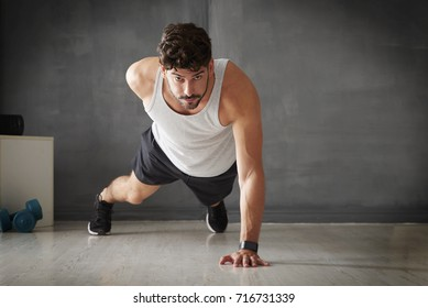 Full length shot of a young man doing a one handed push up in the gym.