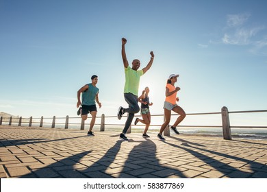 Full length shot of young people running along seaside with young man winning the race.