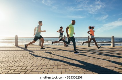 Full length shot of young people running along seaside. Group of runners working out on a road by the sea.
