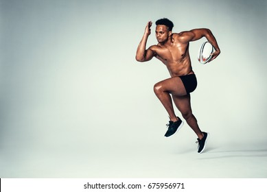 Full length shot of young rugby player training. Muscular male model running with rugby ball on grey background.